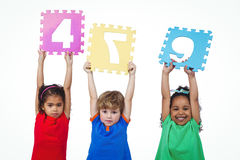 Three kids holding number shanpes above their heads Stock Photos
