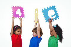 Three kids holding number shanpes above their heads Stock Image
