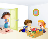 Three kids inside the house with a box of toys Stock Photos