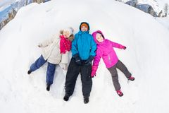 Three kids lay on the snow with legs apart Stock Images