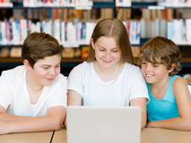 Three kids in library Stock Photography