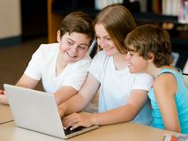 Three kids in library Stock Photos