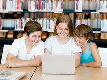 Three kids in library Royalty Free Stock Photo