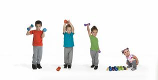 Three kids lifting weights, baby watching stock images