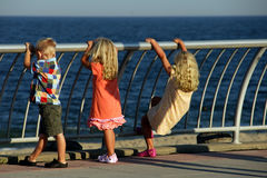 Three Kids looking out to Sea Royalty Free Stock Images