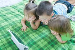 Three kids looking on tablet lying on bed at home. Children time spending. Kids using pad stock image
