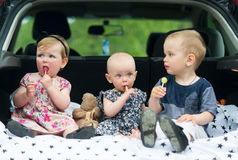 Three kids in luggage carrier of the car eat candies. Royalty Free Stock Photography