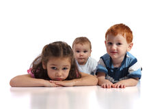 Three kids lying on floor. Isolated white background, foreground reflection Stock Photography