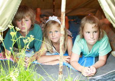 Three kids in an old tent Royalty Free Stock Image