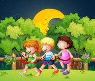 Three kids outdoor walking in the middle of night Stock Photos