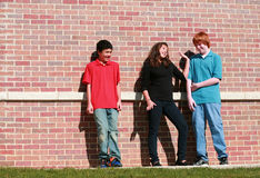 Three kids outside brick wall. Diverse group of multi-ethnic teens talking outside Stock Images