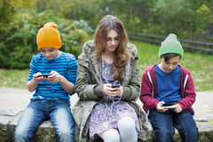 Three kids with phones Stock Image
