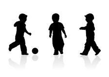 Three kids play ball. Three of kids black contours play ball on the grass on three different backgrounds - green,red and blue Royalty Free Stock Image