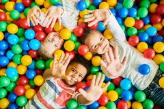 Three Kids Playing in Ballpit. Above view portrait of three happy little kids in ball pit smiling at camera raising hands while having fun in children play royalty free stock image