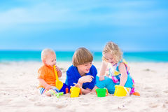 Three kids playing on a beach. Three kids, teen age boy, little toddler girl and a funny baby playing together digging in sand with plastic colorful toys, spade Royalty Free Stock Photo