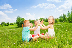 Three kids playing on a grass Stock Photo