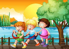Three kids playing inside the ribbon at the wooden bridge Royalty Free Stock Images