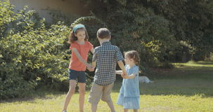 Three kids playing outdoors in the sun stock video footage