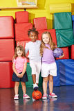 Three kids playing soccer in gym Stock Images