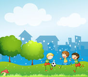 Three kids playing soccer in the hill Royalty Free Stock Photo