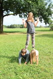 Three kids playing and standing on each other Stock Photo