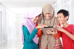 Three kids playing tablet computer Royalty Free Stock Photography
