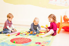 Three kids playing with toys Royalty Free Stock Photos