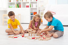 Three kids playing with wooden blocks Royalty Free Stock Images