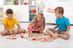 Three kids playing with wooden blocks Royalty Free Stock Photo