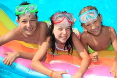 Three kids in the pool Stock Images