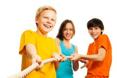 Three kids pull the rope. With smile on their face Stock Photos