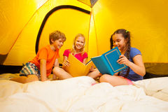 Three kids reading books in a tent Stock Photo