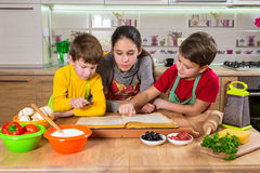 Three kids reading the cook book, making the dinner Royalty Free Stock Photo