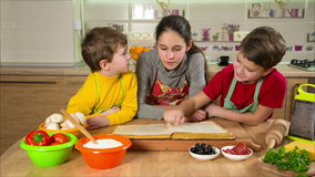 Three kids reading the cook book, making the dinner stock video