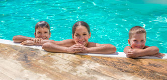 Three kids relaxing on swimming pool Stock Photography