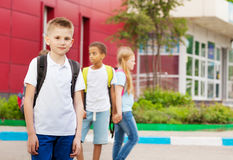 Three kids with rucksacks near school facade Stock Images