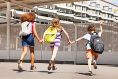 Three kids run to school view from behind. Kids run to school holding hands and wearing backpack royalty free stock images