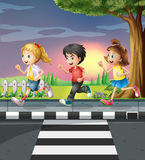 Three kids running along the road Royalty Free Stock Image