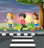 Three kids running along the road Royalty Free Stock Image