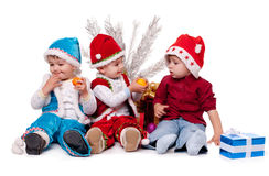 Three kids in Santa hats. Beside Christmas tree Stock Image