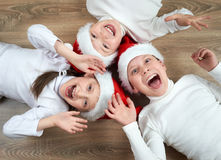 Three kids in Santa hats lying on wooden background, having fun and happy emotions, winter holiday concept Royalty Free Stock Photography