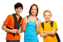 Three kids with school backpacks stock images