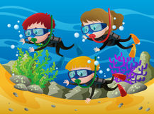 Three kids scuba diving under the sea Stock Image