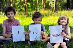 Three kids with a sign I love mum Royalty Free Stock Images