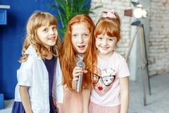 Three kids sing a song in a microphone. Group. The concept is ch. Ildhood, lifestyle, music, singing, friendship stock photos