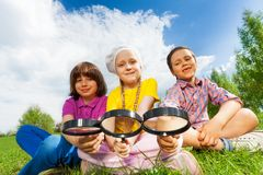 Three kids sitting close together with magnifiers Stock Photo