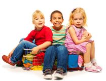 Three kids sitting in the clothes basket Royalty Free Stock Photo