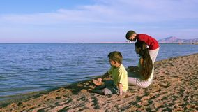 Three kids sitting at the coastline of Red sea in Egypt stock video footage