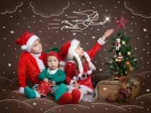 Three kids sitting near Christmas tree dreaming of magic Royalty Free Stock Photo