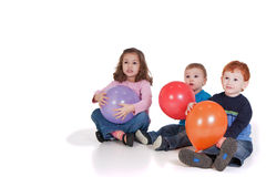 Three kids sitting with party balloons. Three kids sitting down with balloons at party. Isolated on white Royalty Free Stock Photos